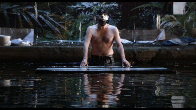 man with a painted face coming out of the water